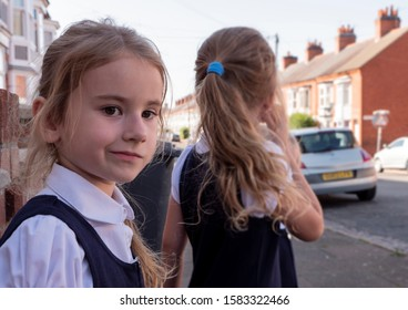 A doubtful looking young girl standing next to another girl, both wearing school uniforms