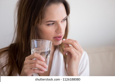Doubtful sick ill young woman holding pill and glass of water taking painkiller medicine drugs to relieve headache pain, worried about side effects of antidepressant or emergency contraceptive meds