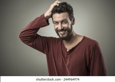 Doubtful smiling young man touching his head and thinking