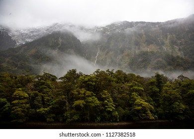 Doubtful Sound New Zealand. Low cloud with waterfalls and ice capped mountains.
