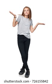 Doubtful teen girl standing in full length with two opened hand palms with blank copy spaces contemplating choosing weighing, isolated on white background