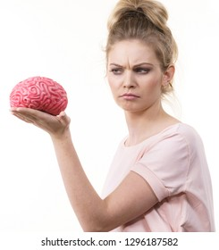 Doubtful woman holding brain having something on mind, trying to understand solution.