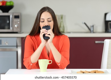 Doubtful woman looking down and wondering if she must call on the phone or waiting for a message in the kitchen at breakfast