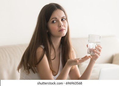 Doubtful young woman feels unsure taking medicine, depressed unhealthy girl holding antidepressant pill, glass of water at home, making decision of emergency contraceptive, worried about side effects