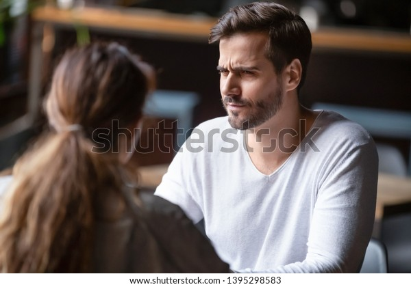 不満を持つ男性が女性を見るのを疑う、初デートの悪いコンセプト、カフェのテーブルに座る若い夫婦、話す、第一印象が悪い、公共の場での知り合い、不愉快な会話