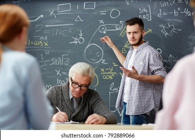 Doubting guy by blackboard pointing at sketch and looking at one of groupmate while waiting for hint