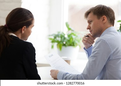 Doubting hr manager looking at applicant at job interview rear view, job seeker answering at employer question, man attentively listen woman, holding resume in hand, thinking about hiring decision