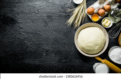 Dough background. Dough with eggs, flour and butter. On black rustic background