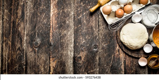 Dough background. Fresh dough with various ingredients on a wooden table.