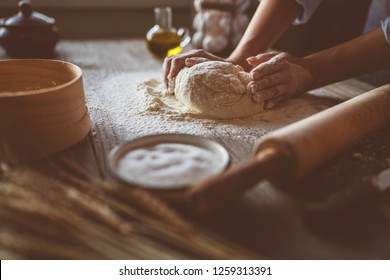 Dough for bread or pizza on a wooden surface with natural light. Hands cooking dough on dark wooden background. Food concept. Selective focus.