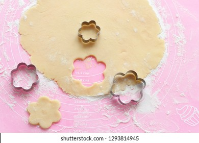 Dough, cookie cutters, flowers on a pink silicone board sprinkled with flour