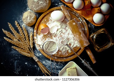 Dough, flour with accessories for the kitchen in the composition on the kitchen table