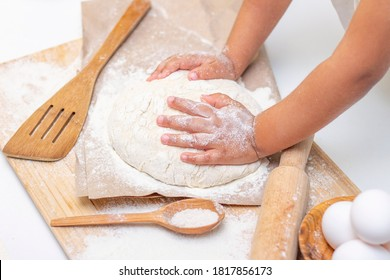 dough in flour kneading childrens hands, one kid, child helps parents in kitchen, concept of a happy childhood, household help, homework, food preparation