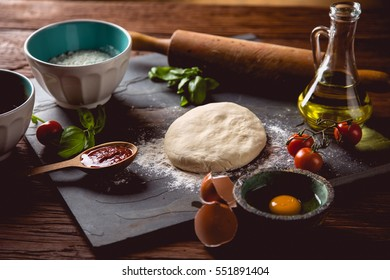 Dough with flour on wooden table, preparing homemade pizza