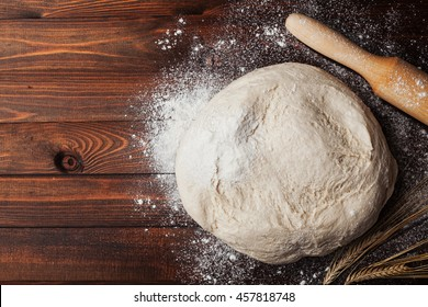 Dough with flour, rolling pin and wheat ears on rustic wooden table from above. Homemade pastry for bread or pizza. Bakery background
