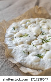 Dough for focaccia. Raw focaccia with olive oil and rosemary. Natural bread dough. Leaven.