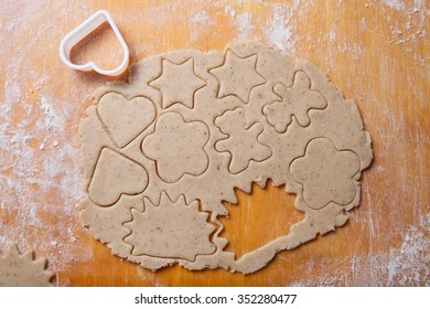 Dough for gingerbread cookie and cookie cutters in different shapes on light wooden cutting board like background.