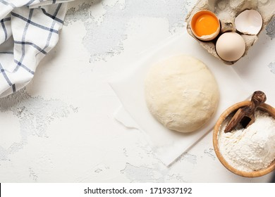 Dough and ingredients for the preparation of pasta, dough, eggs, flour, water and salt on a light rustic old table. Top view.