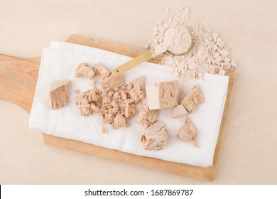 Dough making. Yeast blocks and flour on wooden board on beige background.