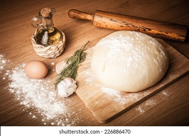 dough on a board with flour. olive oil, eggs, rolling pin, garlic