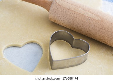 Dough rolled out with heart shape cut out, and heart shaped cookie cutter