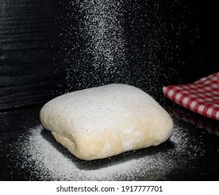 dough sprinkled with flour near a red towel on a dark table