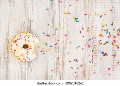 Doughnut on white wood background with colorful sprinkles and bite taken