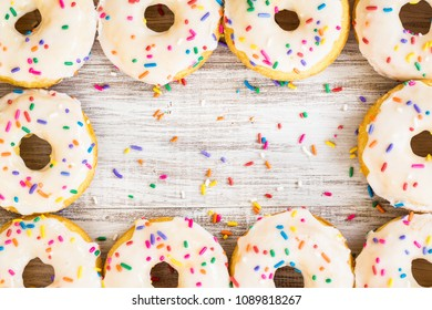 Doughnuts for breakfast arranged on white wooden background with colorful sprinkles