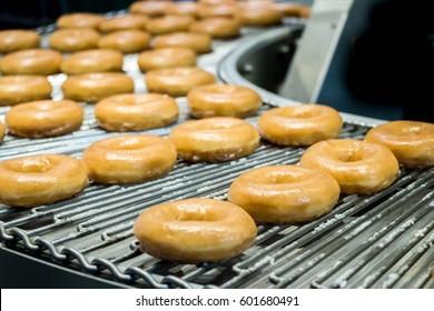 пончики или пончики на конвейерной ленте на фабрике, вид жареного теста кондитерских изделий или десертной пищи. -Изображение