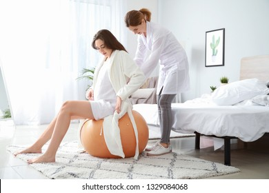 Doula massaging pregnant woman at home