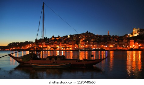 Douro river and traditional boats at night in Oporto, Portugal