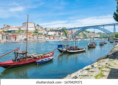 Douro river and traditional boats with wine barrels and Luis Bridge in Porto from Vila Nova de Gaia, Portugal cityscape