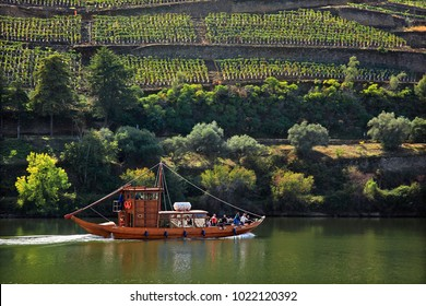 "DOURO VALLEY, PORTUGAL- October 9, 2015. Cruising river Douro with a traditional boat called ""barco rabelo""."