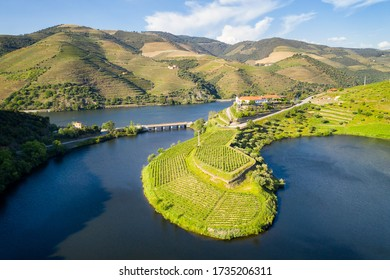 Douro wine valley region drone aerial view of s shape bend river in Quinta do Tedo at sunset, in Portugal