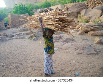 DOUROU, MALI - DEC 30: A little girl stops while carrying a heavy bundle of wood over her head on December 30, 2009 in a Dogon village near Dourou, Mali