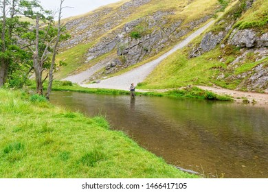 Dovedale, Derbyshire - July 26 2019: A fisherman standing in the shallow water of the River Dove in the Derbyshire Peak District
