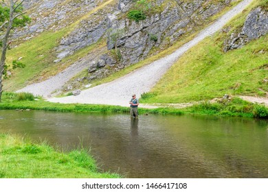 Dovedale, Derbyshire - July 26 2019: A fly fisherman standing in the River Dove casts his line out.