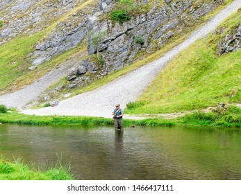 Dovedale, Derbyshire - July 26 2019: A fisherman standing in the River Dove preparing to cast his line in to the clear water.