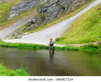 Dovedale, Derbyshire - July 26 2019: A fly fisherman standing in the River Dove, in Dovedale reels his line in