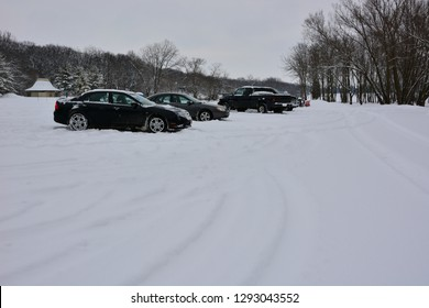Dover, Wisconsin / USA - January 23, 2019: Cars and trucks parked in the Eagle Lake County Park parking lot during a winter snowfall.