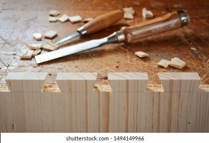 Dovetail joint on working table. Chisel and wood chips. Detail of wood joinery in spruce wood. Picture taken in woodworking workshop.