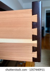 Dovetailed detail on a side of a dressed drawer. A dovetail joint or simply dovetail is a joinery technique most commonly used in woodworking joinery including furniture, cabinets.