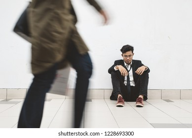 dowdy young asian businessman sitting at walkway thinking of his problem and look so depressed while people passing by ( motion blur )
