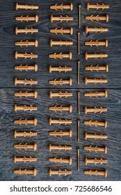 Dowels lying in rhythm on dark wooden background