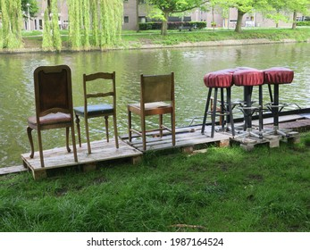 down by the waterfront, chairs and bar stools near a canal in Amsterdam