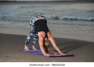 Down Dog Yoga pose in pattern tights along coastline.