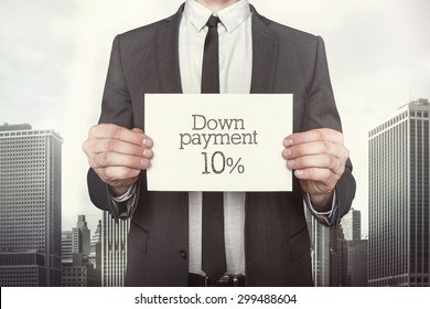 Down payment 10 percent on paper what businessman is holding on cityscape background