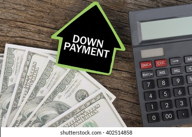 """""""DOWN PAYMENT"""" Word on House with Calculator and Dollars On Wood Background, Costing and Budget Concept"""