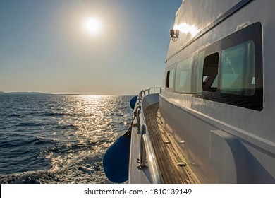 Down down side of luxury yacht travelling across open ocean with sunsrise at dawn