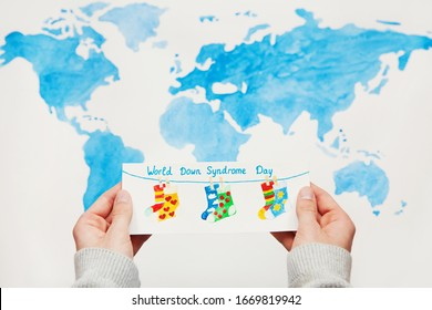 """Down syndrome concept. Watercolor illustration with pairs of multi-colored socks and text """"World Down Syndrom Day"""" in hands of child on background of world map"""